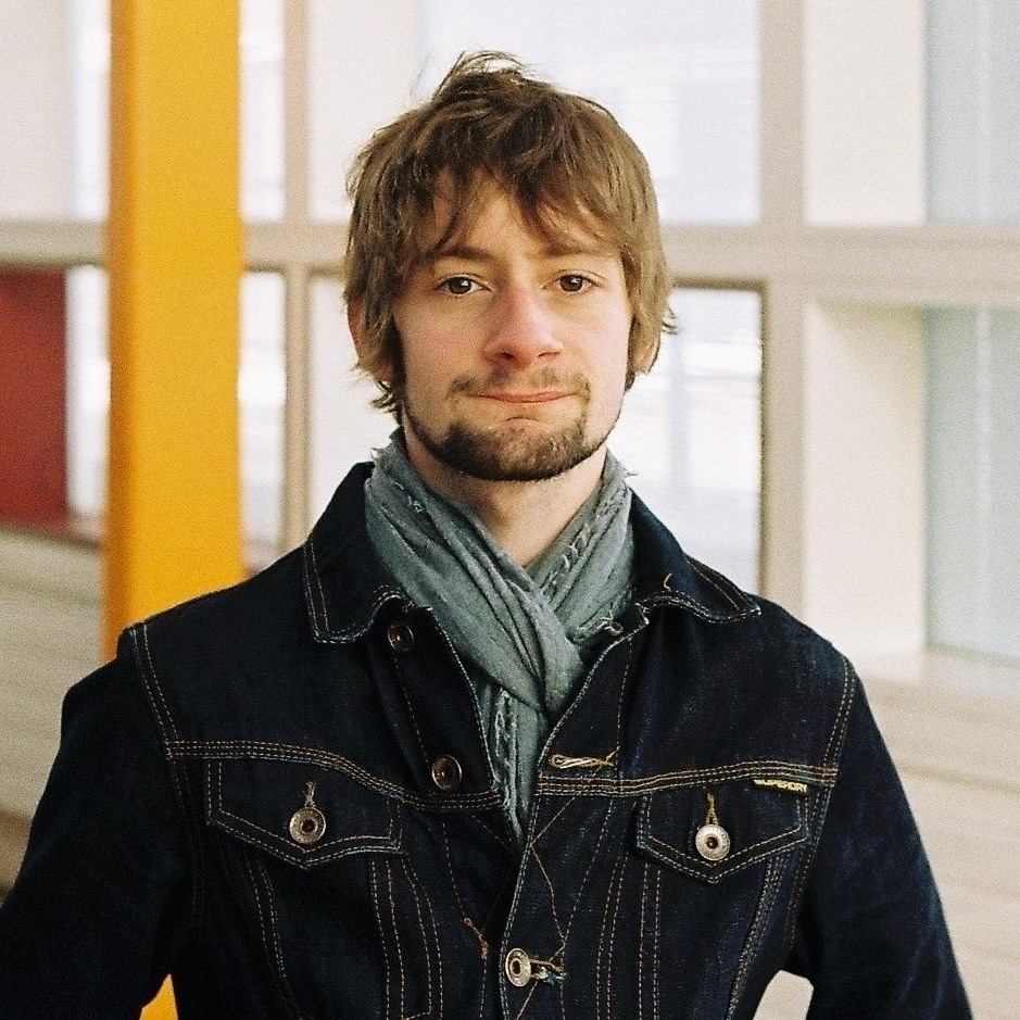 Oliver poses for the camera. He has mice brown hair that falls over his ears down to his cheekbones and a short beard. He wears a grey-blue scarf and a dark-blue denim jacket.