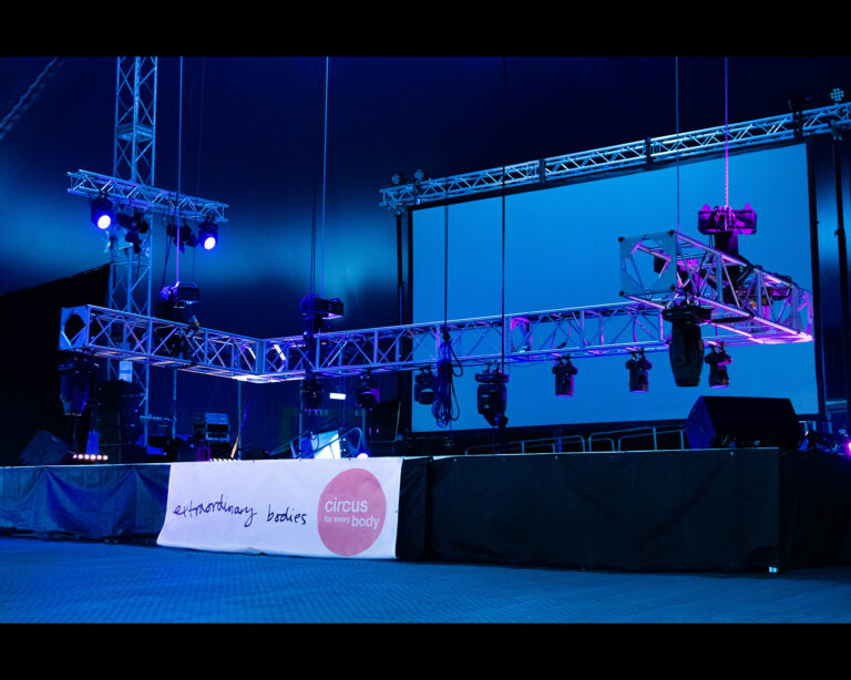 """An empty stage lit up by dim blue and purple light. Rigging and spotlights are just above the stage level. In front of the stage, a white banner with a black """"Extraordinary Bodies"""" logo with a light red circle to the right with white words in it that read: """"Circus for Every Body""""."""