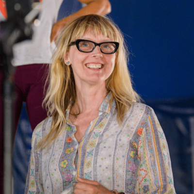 Hattie: a white woman in her fifties with long blonde hair and a fringe, thick black secretary-style glasses and a colourful shirt. She smiles brightly.