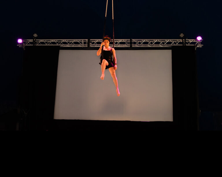 A woman in her twenties with light brown skin and afro hair twisted into a half-up half-down style sits on a trapeze, flying in the air. One of her legs is bent and pointing towards us. Behind her, steal rigging and purple lights and a white screen.