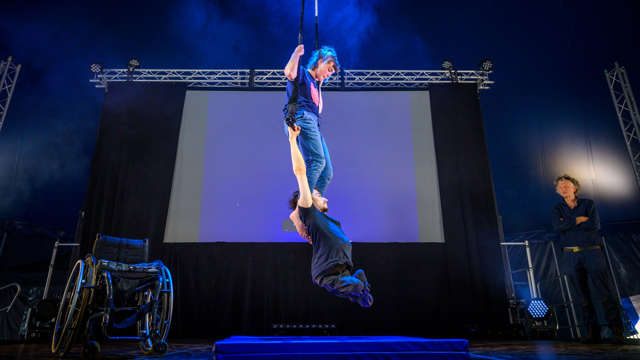Indoors circus stage. A white woman in her twenties sits on a trapeze, her hands holding the ropes on each side. A white man in his twenties and wheelchair user holds himself up in the air below her by holding onto the trapeze bar. Her legs extend down to his upper back, her feet by his shoulders.