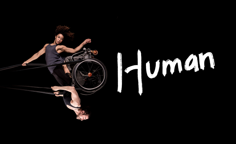 Black background. A photo of a woman and a man swinging in the air like a pendulum, looking powerful and graceful. They share a wheelchair which is held up in the air by black circus straps. She has frizzy brown hair, muscular arms and wears a grey tank top She is sitting on knees on his thighs and one of her arms holds the straps above her head while the other points down towards the floor. He has a neatly trimmed brown beard, muscular arms and wears a black tank top. He holds the straps to the sides of his chest with both hands. The image captures them at the highest point of the swing, to our right, bringing the man to an upside-down position with the woman above him. Their bodies are doing something hard, but their strength makes it look effortless. One word written in white, thick, brush-style letters to the right of the photo: 'Human'.