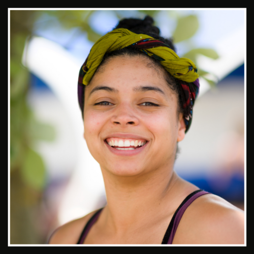 Rebecca: a woman in her twenties with light brown skin and afro hair twisted into a half-up half-down style, a green and red headband twisted around her head. She is smiling brightly at the camera.