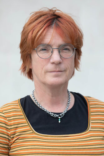 Headshot of Abi, a white woman with short hair dyed orange, round and thin-rimmed glasses. She has a nose ring and wears a thick chain around her neck.