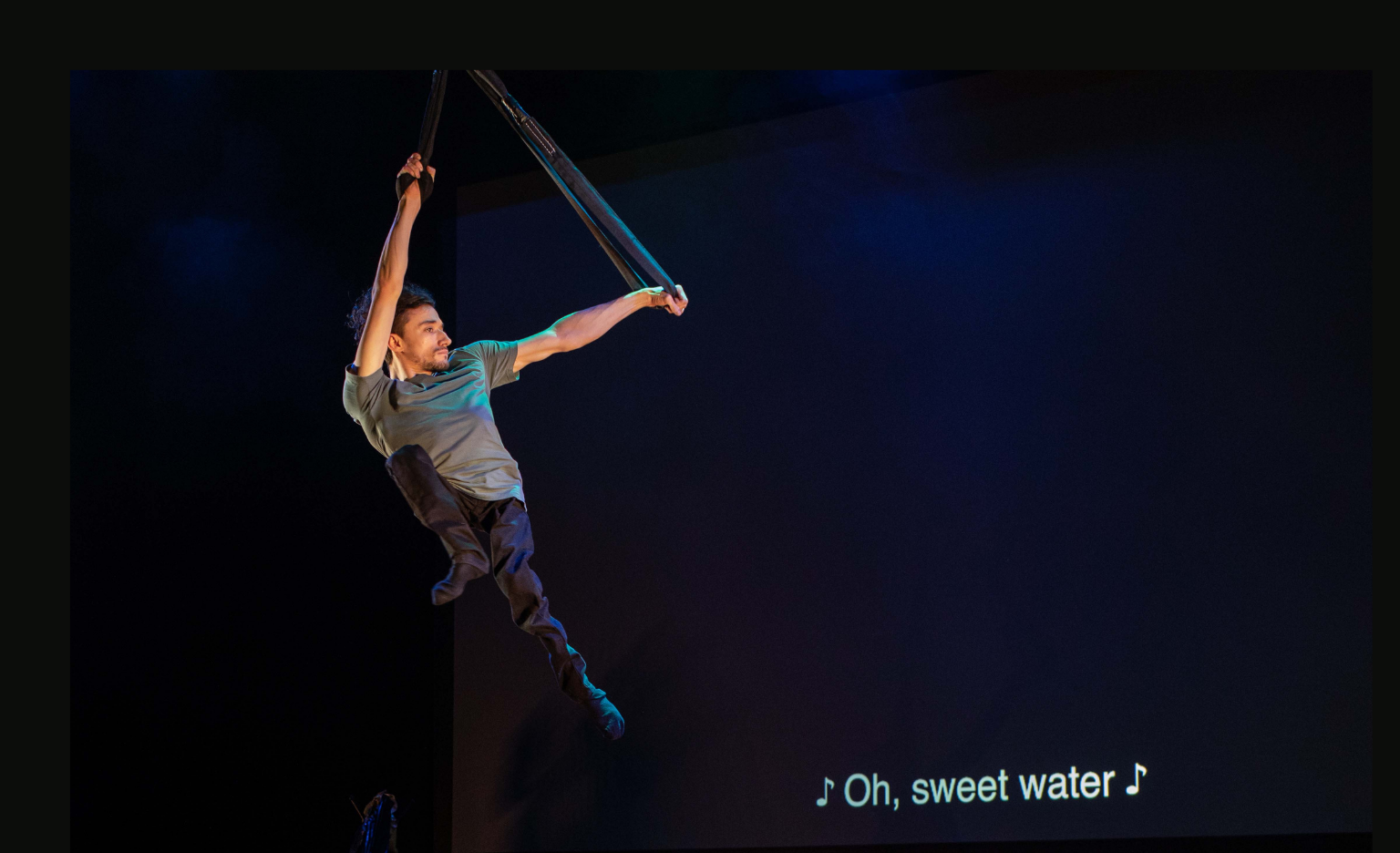 """A white man in his twenties in the air above the the stage by holding onto black straps. He wears a grey T-shirt and black trousers. His thin legs dangle below him as he flies, looking strong. In the background, white text on a black screen tells us that a song is playing in this moment, with the following lyrics: """"Oh, sweet water""""."""