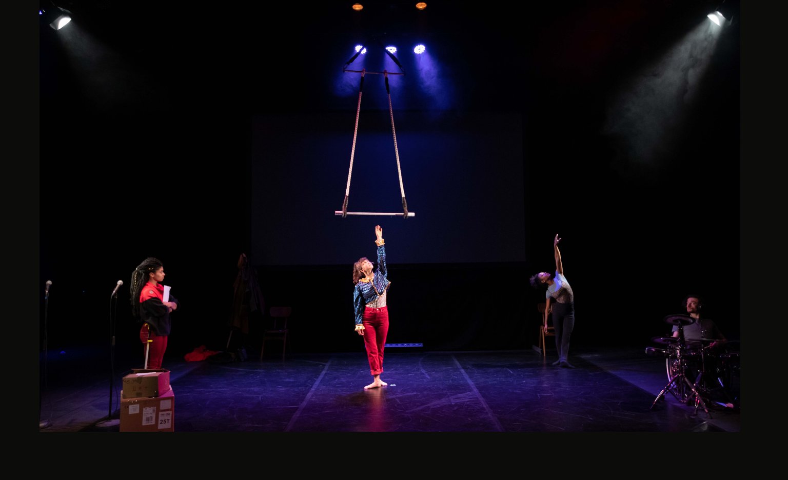 Three performers on a dimly lit bare stage, purple spotlights above them. In the centre, a white woman in her twenties stands with one arm raised up to a trapeze that hangs from above. She wears a blue and gold sparkly top and red trousers. On the left, a mixed-race woman in her twenties wears a DPD delivery outfit - black and red fleece top and red trousers. She looks at the performer in the centre. On the right, a mixed-race woman stands with one arm raised up, bending backwards gracefully. She wears a leotard and grey leggings.