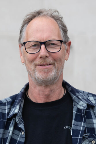 Headshot of James: A middle-aged man with grey hair, a white stubble beard, black-framed glasses. He is wearing a blue and white checked shirt and is smiling softly at the camera.