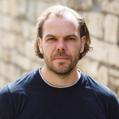 Steven: a white man with ear-length, wavy, brown hair and a brown stubble beard, wearing a dark blue t-shirt. He is standing outside, smiling softly at the camera, the sun touching the top of his head.
