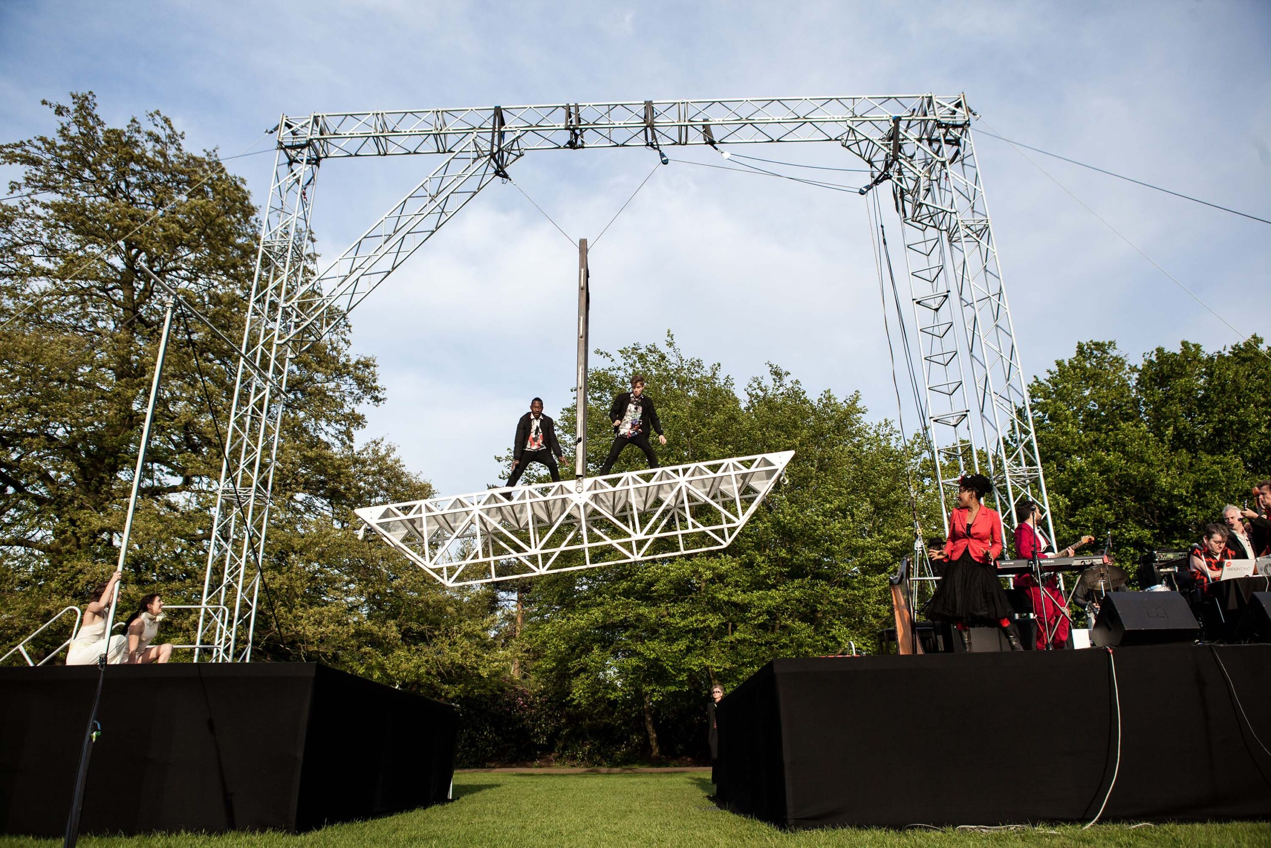 An outdoors circus stage with tall steel rigging. Two men stand on opposite ends of a 6 meters long bridge made of white metal. It is up in the air and acting as a balance, held in its centre by a large metal bar that allows it to balance to the left and to the right.