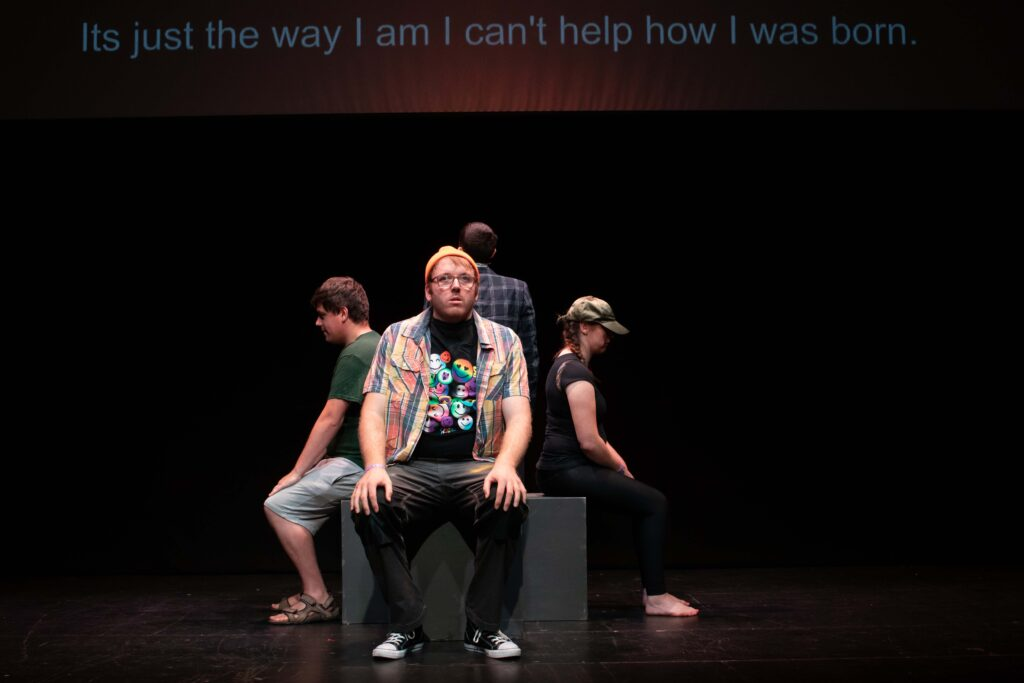 """A group of young people sitting on a black block on a dimly lit stage. Each one of them sits on a different side of the block, back to back, looking pensive. Behind them, captions on a screen read: """"It's just the way I am I I can't help how I was born."""""""