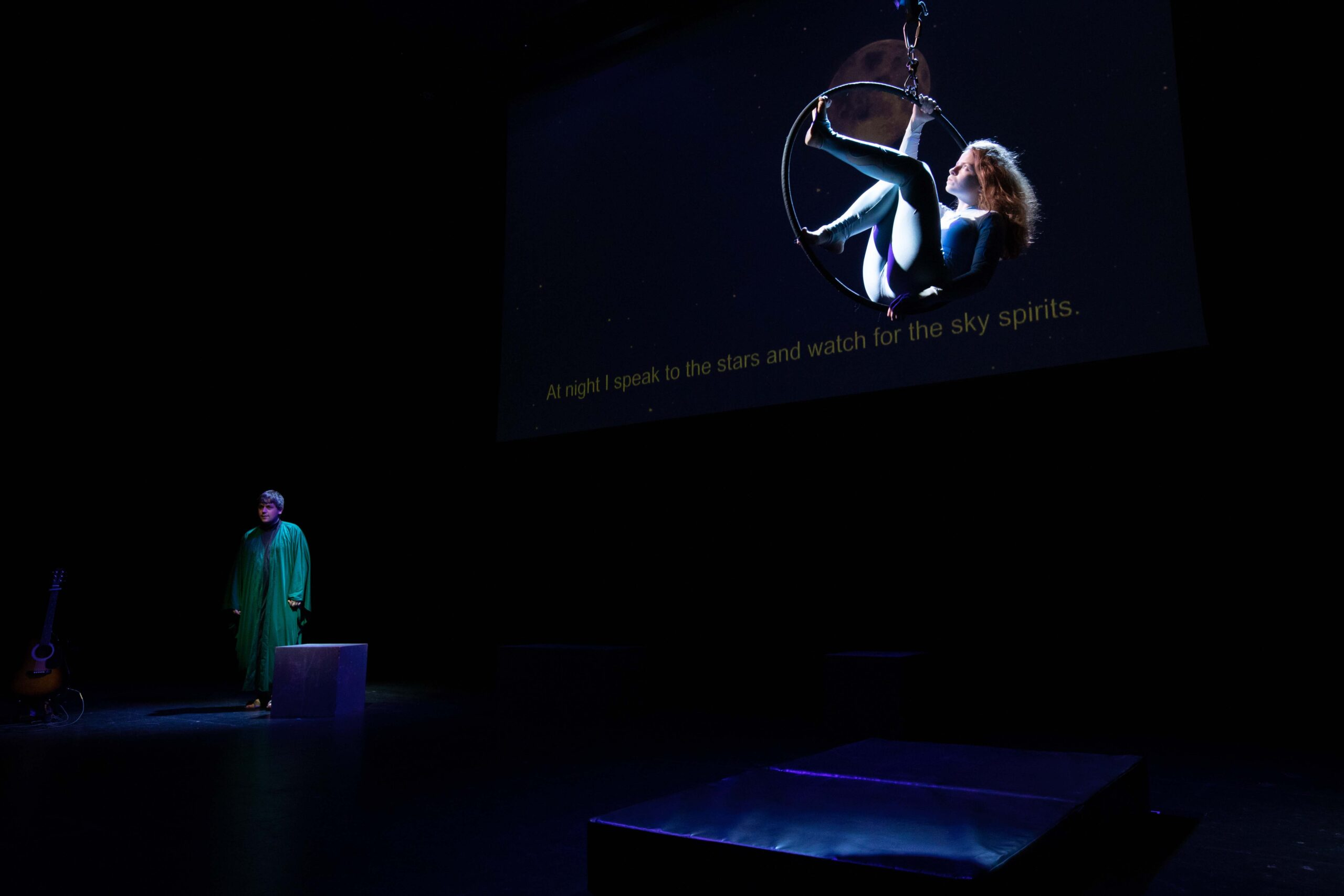 A dimly-lit stage, with soft, deep blue light on two performers. The first one is in the foreground, sitting delicately on a circus hoop that holds them up in the air. They are female-presenting, with long golden hair and a light blue lycra one piece. In the background, a male-presenting performer is dressed like a priest. They stand, looking ahead of them towards the audience.