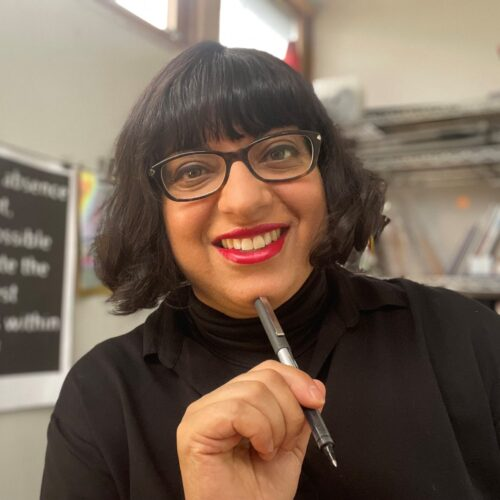 Binita is a middle-aged Indian woman with bobbed black hair and a fringe. She wears brown rectangular glasses, red lipstick and wears black a lot.